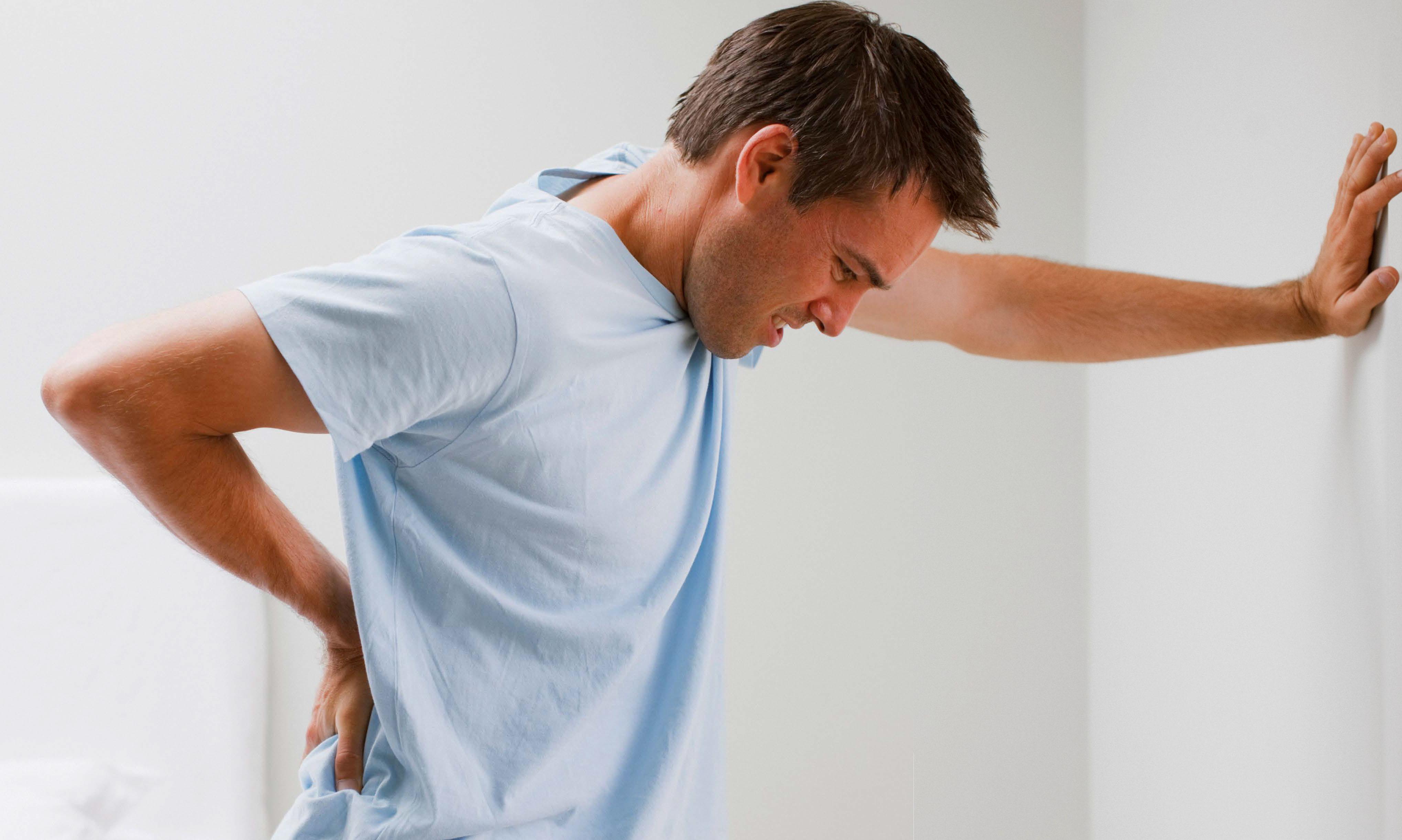 Ein Mann stützt sich mit Rückenschmerzen an der Wand ab. Gegen Rückenschmerzen StimaWEll.